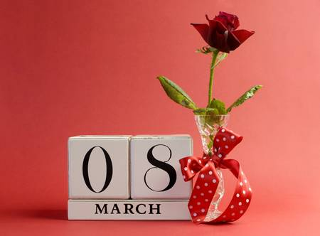 Red theme Save the Date white block calendar for International Women s Day, March 8, decorated with flower, vase and polka dot ribbon  Stock Photo