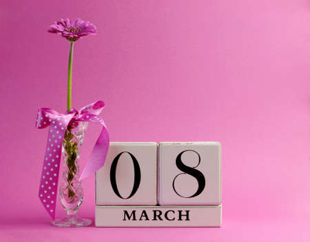 8 march: Pink theme Save the Date white block calendar for International Women s Day, March 8, decorated with flower, vase and polka dot ribbon  Stock Photo