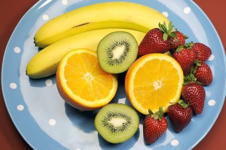naturopath: Platter of fruit - bananas, orange, kiwi fruit and strawberries - on blue polka dot platter for healthy diet and fitness