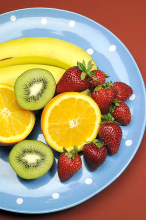 naturopath: Platter of fruit - bananas, orange, kiwi fruit and strawberries - on blue polka dot platter for healthy diet and fitness  vertical  Stock Photo
