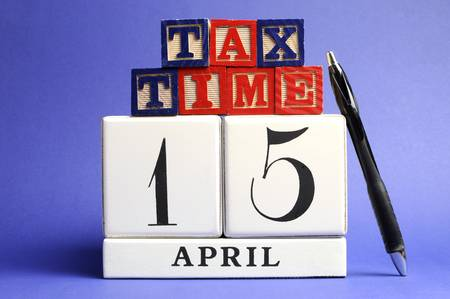 dat: Save the Date, April 15, USA Tax Day with white calendar and red, white ad blue building block letters on blue background