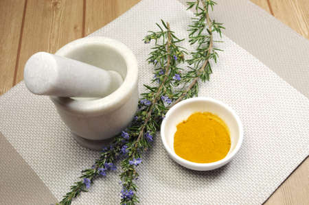 Rosemary herb and turmeric spice with mortar and pestle for cooking or health preparation on wood table  photo