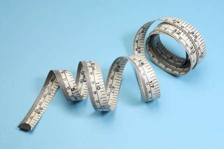 herbolaria: Cinta m�trica blanca sobre fondo azul para bajar de peso y la dieta de p�rdida de peso o el concepto de fitness Foto de archivo