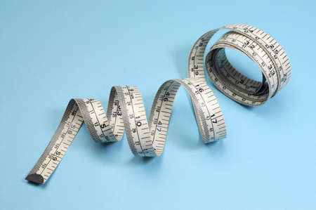 naturopath: White tape measure on blue background for slimming and weight loss diet or fitness concept