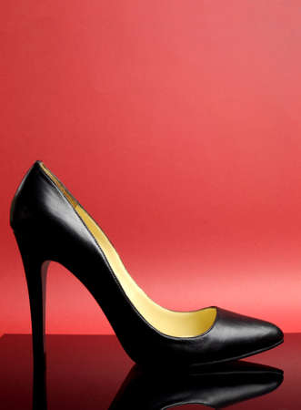 Black stiletto high heel female shoe on red background for iconic symbol of women, feminitity, fashion and beauty - vertical with copy space for your text here  photo
