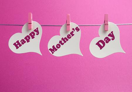 Happy Mothers Day message written across white heart shape gift tags hanging from pegs on a line against a pink background  Stock Photo