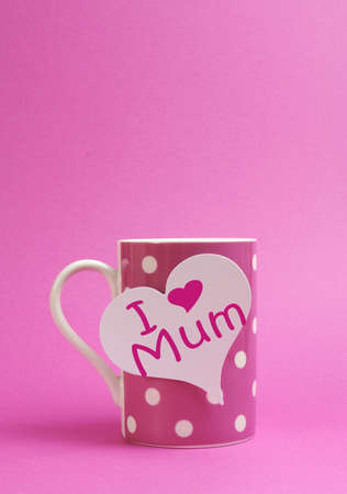 mothering: Pink polka dot coffee or tea mug with heart shape white gift tag with I Heart Love Mum for Mothers Day on pink background with copy space for your text here