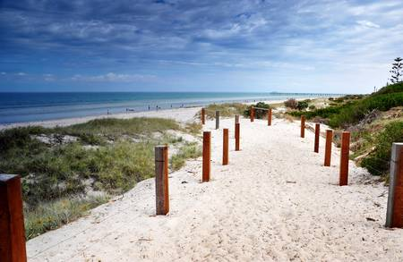 Path leading down to Henley Beach, South Australia, showing white sandy beach, jetty in background, and clean blue ocean  photo