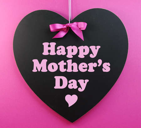 mothering: Heart shape blackboard with pink ribbon on pink background with Happy Mothers Day message