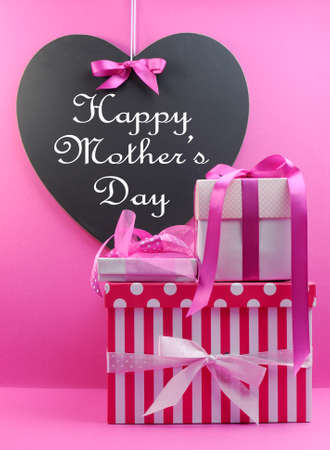 mothering: Stack of beautiful pink stripe and polka dot present gifts with heart shape blackboard with Happy Mothers Day message