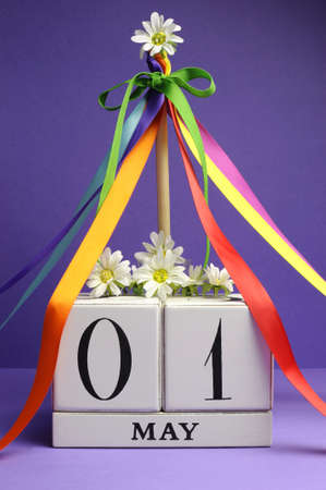may: May Day, May 1, white block calendar with maypole and rainbow color ribbons and flowers against a purple background