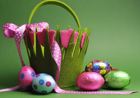 Happy Easter, Easter egg hunt with colorful Spring theme polka dot carry basket bag and chocolate Easter eggs on green background  photo