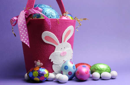 Easter Sunday egg hunt with pink felt bag with white bunny rabbit and colorful chocolate and painted eggs on purple background. Stock Photo