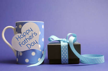fathers day: Happy Fathers Day message written on white heart gift tag on blue polka dot mug with black box gift against a blue background