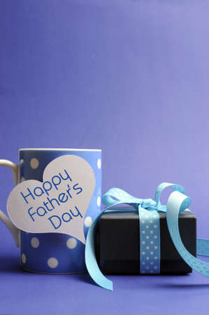 Happy Fathers Day message written on white heart gift tag on blue polka dot mug with black box gift against a blue background  Vertical - with copy space  photo