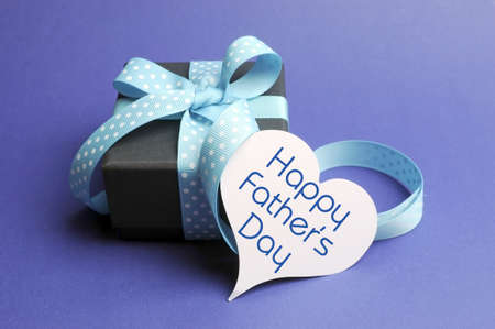 heart gift box: Blue theme black box present gift with polka dot ribbon and white heart shape tag with Happy Fathers Day message Stock Photo