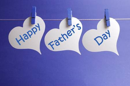 Happy Fathers Day message written on white heart shape tags hanging from blue pegs on a line against a blue background  Stock Photo