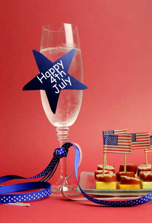 USA Happy Fourth 4th of July party table setting with flags, ribbons, polka dots, and stars and stripes champagne glass and cocktail food  Vertical Stock Photo - 18909083