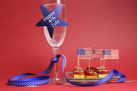 USA Happy Fourth 4th of July party table setting with flags, ribbons, polka dots, and stars and stripes champagne glass and cocktail food Stock Photo - 18909124
