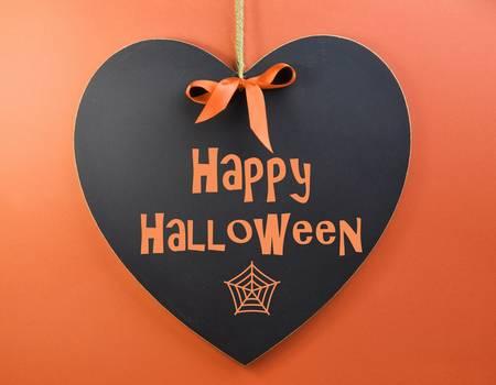 happy halloween: Happy Halloween message written on heart shape blackboard against an orange background  Stock Photo