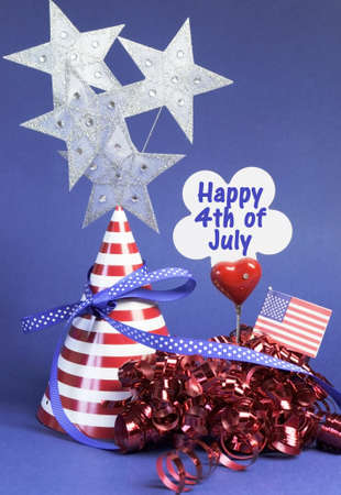 Happy Fourth 4th of July party table decorations with hat, streamers, sign, flag and stars in USA America red, white and blue theme. Vertical. photo