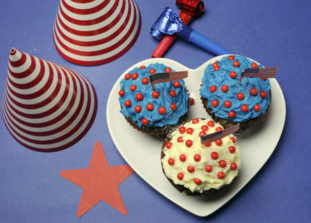 Fourth 4th of July party celebration with red, white and blue chocolate cupcakes on white heart plate and USA American flags with party table setting decorations Stock Photo - 18909141