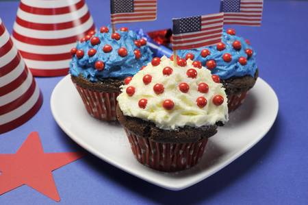 Fourth 4th of July party celebration with red, white and blue chocolate cupcakes on white heart plate and USA American flags - closeup  Stock Photo - 18909137