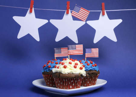 Fourth 4th of July party celebration with red, white and blue chocolate cupcakes on white heart plate and USA American flags with stars hanging from pegs on a line with copy space  Stock Photo - 18909134