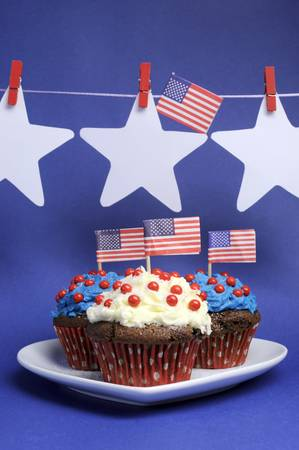 Fourth 4th of July party celebration with red, white and blue chocolate cupcakes on white heart plate and USA American flags with stars hanging from pegs on a line with copy space  Vertical  Stock Photo - 18909135
