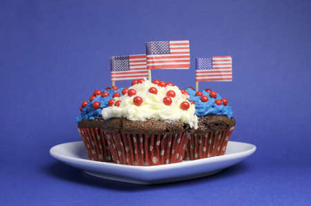 Fourth 4th of July party celebration with red, white and blue chocolate cupcakes on white heart plate and USA American flags Stock Photo - 18909143