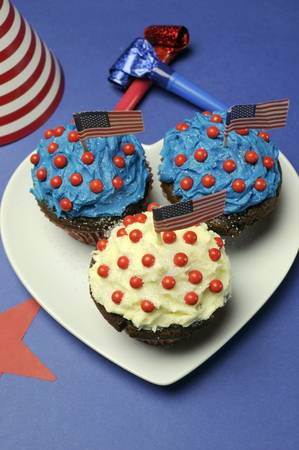Fourth 4th of July party celebration with red, white and blue chocolate cupcakes on white heart plate and USA American flags with party table setting decorations  Vertical Stock Photo - 18909140