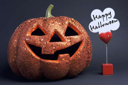 Happy Halloween orange color fun pumpkin with scary face and red heart sign and message on black background  photo