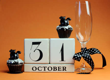 Happy Halloween save the date white block calendar with champagne glass and chocolate muffins with black cat decorations and polka dot ribbon on orange background  photo