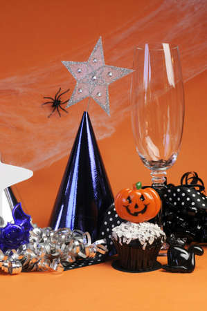 Happy Halloween party decorations with cobweb and spider, champagne glass, hats, chocolate cupcake, stars and streamers on orange background  Vertical  Stock Photo - 18952354