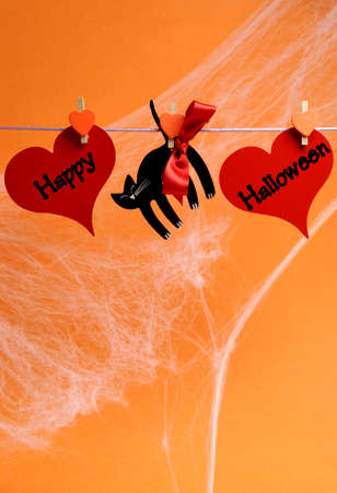 Happy Halloween message written across red hearts and black cat with pegs hanging from a line against an orange background  Vertical with copy space for your text here  photo