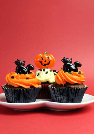 Happy Halloween ornage and black decorated cupcakes with black cats and jack-o-lanterns on white heart plate against a red background. Vertical with copy space for your text here. photo
