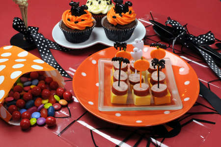Happy Halloween party table with skeleton glass, cupcakes, candy lollies and party food with orange and black pumpkin, cat, bat and ghost decorations. photo