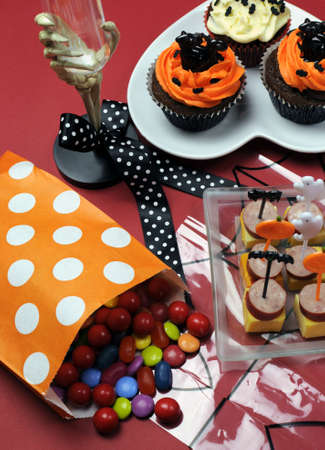 Happy Halloween party table with skeleton glass, cupcakes, candy lollies and party food with orange and black pumpkin, cat, bat and ghost decorations. Stock Photo - 19057047