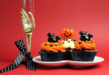 treating: Happy Halloween party food with skeleton hand glass on red background. Stock Photo