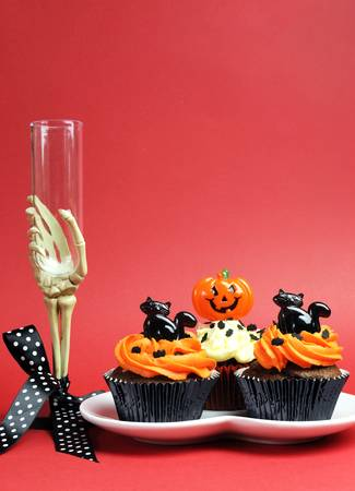 31: Happy Halloween party food with skeleton hand glass on red background, with cupcakes. Vertical with copy space..