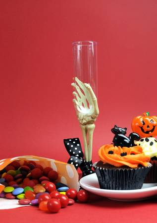 Happy Halloween party food with skeleton hand glass on red background, with cupcakes and candy lollies. Vertical with copy space. photo