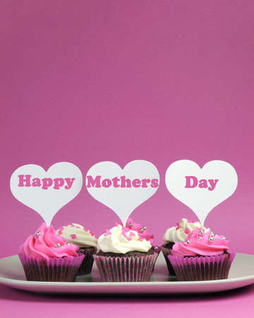 mothering: Happy Mothers Day message written across white heart toppers on pink and white decorated cupcakes - vertical with copy space for your text here