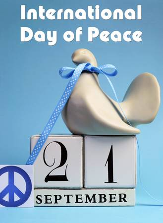 peace sign: Dove and Peace Sign decorations for International Day of peace, World Peace Day, with white block calendar date on pale blue background  Vertical with title message text  Stock Photo