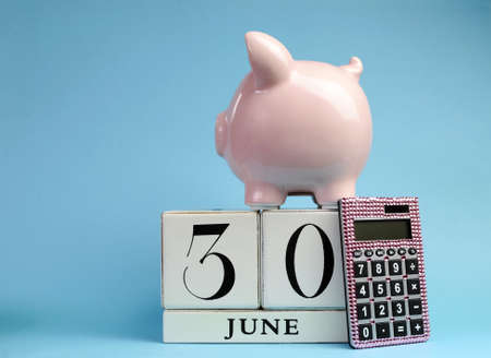 exemption: Calendar date for End of Financial Year, 30 June, for Australian tax year or retail stocktake sales, with piggy bank and pink calculator on sky blue background, with copy space.