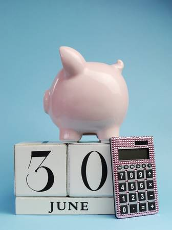 Calendar date for End of Financial Year, 30 June, for Australian tax year or retail stocktake sales, with piggy bank and pink calculator on sky blue background, with copy space. Vertical view.