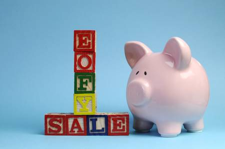 the end of the year: End of Financial Year sale message on building blocks with piggy bank on pale blue background.