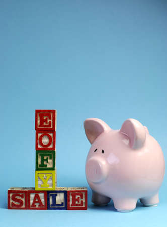 exemption: End of Financial Year sale message on building blocks with piggy bank on pale blue background. Vertical with copy space for your text here.