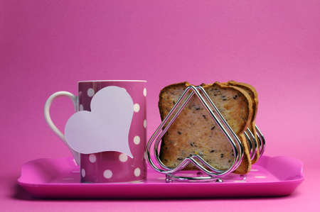 Pink breakfast tray with polka dot coffee tea cup mug and heart shape toast rack with wholemeal toast for Mothers Day, birthday or Pink Ribbon charity breakfast with heart tag for your text here. photo