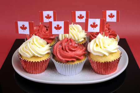 canada day: Red and White cupcakes with Canadian maple leaf national flags against a red background for Canada Day or Canadian national holidays. Close-up.