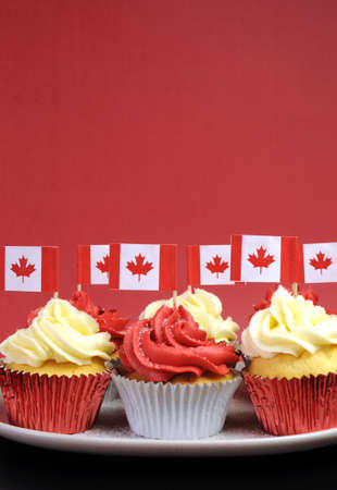 canada day: Red and White cupcakes with Canadian maple leaf national flags against a red background for Canada Day or Canadian national holidays. Vertical with copy space for your text here.